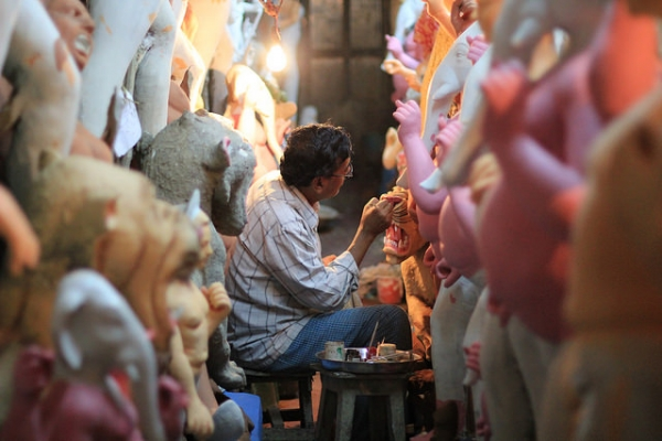 A potter hard at work painting a long row of religious statues made of clay in Kolkata, India on October 10, 2015. (@DaskBlogs/Flickr)