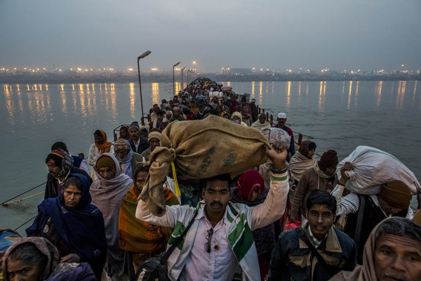 Hindu pilgrims walk across a pontoon bridge as others bathe on the banks of Sangam, the confluence of the holy rivers Ganges, Yamuna, and the mythical Saraswati, during the Maha Kumbh Mela on February 12, 2013 in Allahabad, India. (Daniel Berehulak/Getty Images)