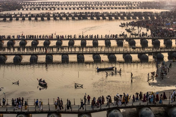 Hindu pilgrims make their way over pontoon bridges near Sangam, the confluence of the holy rivers Ganges, Yamuna and the mythical Saraswati, during the Maha Kumbh Mela on February 9, 2013 in Allahabad, India. (Daniel Berehulak/Getty Images)