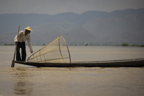 A man adjusts the fishing net on his boat in Yawnghwe, Myanmar on October 24, 2015. (Eric Montfort/Flickr)
