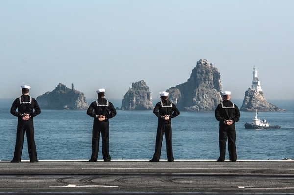 Four navy members stand facing the sea in Busan, South Korea on November 4, 2015. (Official U.S. Navy Page/Flickr)