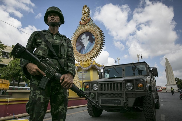 A Thai soldier stands in front of a portrait of King Bhumibol Adulyadej as he patrols near government buildings on May 23, 2014 in Bangkok, Thailand. (Paula Bronstein/Getty Images)