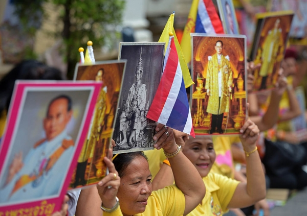 Thai well-wishers hold portraits of Thai King Bhumibol Adulyadej while waiting in front of Siriraj hospital in Bangkok on May 5, 2015. (Pornchai Kittiwongsakul/AFP/Getty Images)