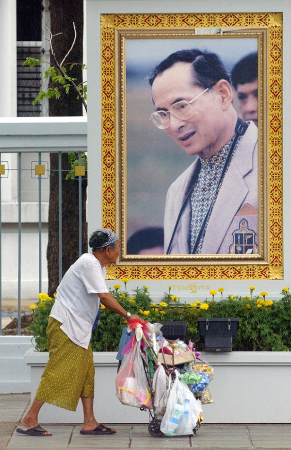 An elderly Thai woman walks past a portrait of King Bhumibol Adulyadej near the Grand Palace in Bangkok on June 10, 2006. (Adek Berry/AFP/Getty Images)