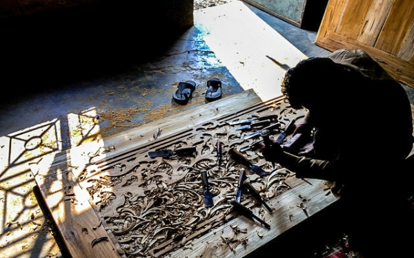 A carpenter uses a myriad of tools to carve out intricate designs on a wooden door in Dhaka, Bangladesh on January 16, 2016. (Md. Aktar Hossain Ratan/Flickr)