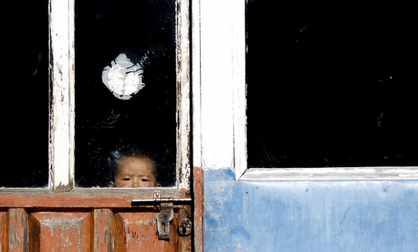 A child peeks out through the glass pane of an old wooden door in Nepal on January 2, 2016. (MIRKO MARCHETTI/Flickr)