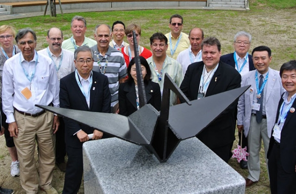 Participants in an exchange between 9/11 and 3/11 survivors pose in Kaisezan Park, Koriyama, Fukushima Prefecture with a steel origami crane in 2013. The crane was fashioned from World Trade Center wreckage and presented by the 9/11 Tribute Center on the first outreach trip in 2012. (9/11 Tribute Center)