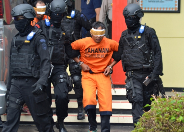 Indonesian anti-terror policemen transfer one of five men (C) following raids related to terror in Malang on February 21, 2016. (Aman Rochman/AFP/Getty Images)