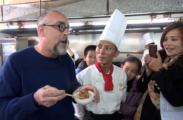 Howie Southworth slurps pork trotters with Chef Yang Jiaquan at the Qianhe Hotel in Qilin, Yunnan, China. (Howie Southworth)