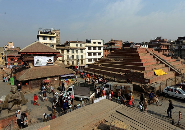 Pedestrians walking by earthquake-damaged buildings in Durbar Square in Kathmandu on April 23, 2016. (Prakash Mathema/AFP/Getty Images)