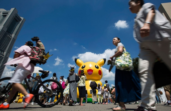 People walk past a Pikachu-shaped balloon during the Pikachu Outbreak  on August 7, 2016 in Yokohama, Japan. (Tomohiro Ohsumi/Getty Images)