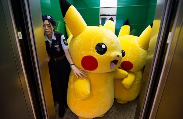Performers dressed as Pikachu, a character from Pokémon series game titles, ride on an elevator during the Pikachu Outbreak event hosted by The Pokémon Co. on August 7, 2016 in Yokohama, Japan. (Tomohiro Ohsumi/Getty Images)