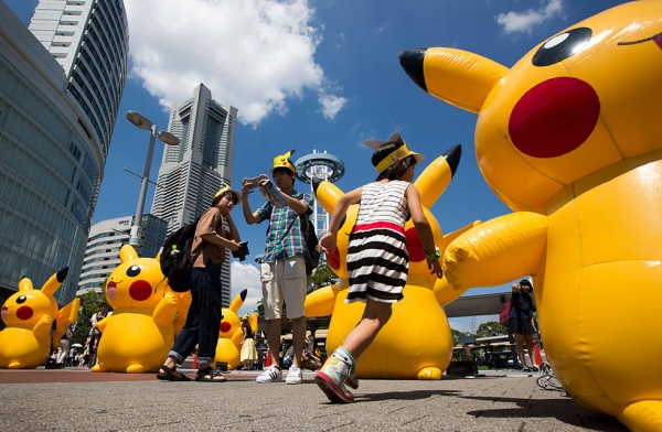A girl runs past Pikachu- shaped balloons as a couple takes a photograph. (Tomohiro Ohsumi/Getty Images)