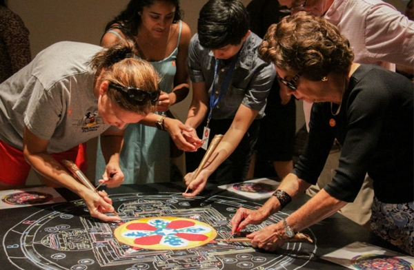 Museum-goers try their hand at using the chakpur, a traditional Tibetan tool used to create sand mandalas, at Asia Society Texas on August 25, 2016. Asia Society Texas hosted Tibetan Buddhist monks from Drepung Loseling Monastery in India to create the mandala in addition to other performances. (Asia Society/Nikki Tripp)