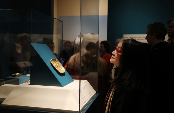 "An attendee examines an artifact in the exhibition ""Secrets of the Sea: A Tang Shipwreck and Early Trade in Asia"" at Asia Society New York on March 6, 2017. (Ellen Wallop/Asia Society)"