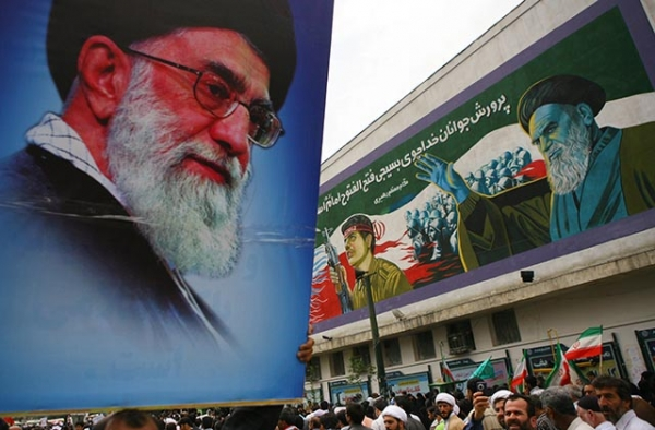 A pro-government demonstrator holds aloft a picture of Ayatollah Ali Khamenei at Tehran University. (Getty)