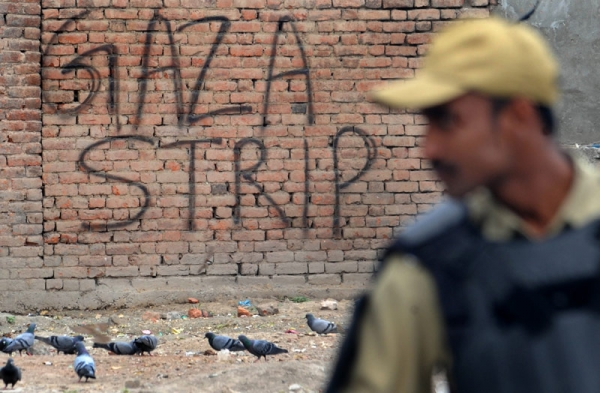 An Indian paramilitary trooper stands guard in front of a wall bearing the grafitti 'Gaza Strip' during an undeclared curfew in Srinagar on May 21, 2011. Authorities in restive Indian Kashmir placed separatist leaders under house arrest to thwart a rally marking the anniversaries of the killing of two of the independence movement's key figures. (Rouf Bhat/AFP/Getty Images)