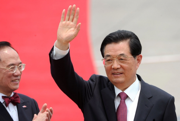 Chinese President Hu Jintao (R) waves to the press as Hong Kong Chief Executive Donald Tsang claps after arriving at Hong Kong's International airport on June 29, 2012. (Dale de la Rey/AFP/GettyImages)