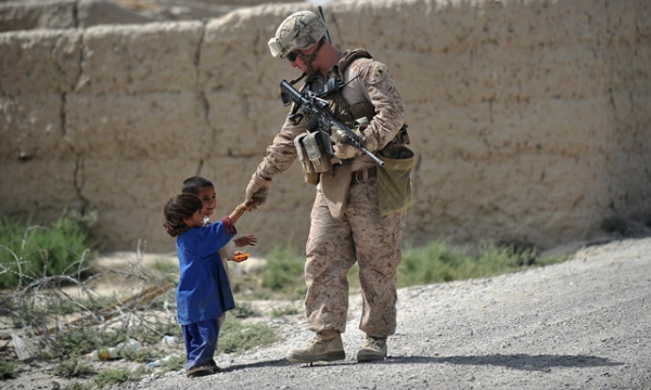US Marine Sgt. Cody Turpen from Kilo Company of the 3rd Battalion 8th Marines Regiment shakes hand with Afghan children during a patrol in Garmser district in southern Helmand Province on June 22, 2012. (Adek Berry/AFP/GettyImages)