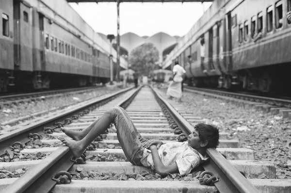 A young boy takes a nap on the rails in Dhaka, Bangladesh on September 21, 2012. (BatulTheGreat/Flickr)