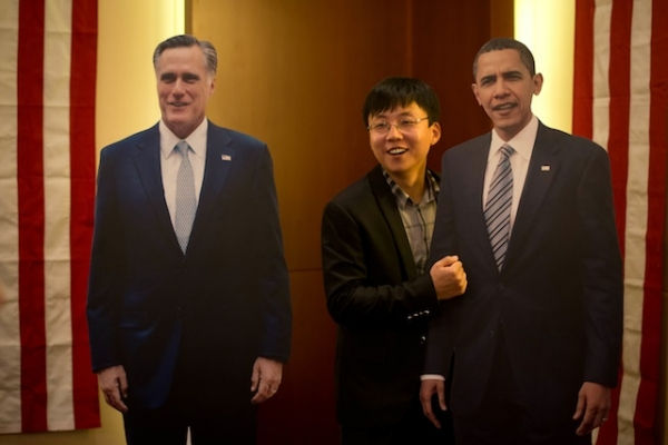 A man poses with cardboard cut-outs of U.S. President Barack Obama (R) and presidential candidate Mitt Romney (L) at a hotel during a U.S. presidential election results event organized by the American embassy in Beijing on Nov. 7, 2012. (Ed Jones/AFP/Getty Images)