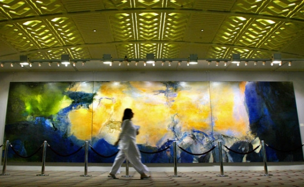 A woman walks past the world's largest triptych ever, produced by painter Zao Wou-ki and displayed at the Christie's Hong Kong Spring Auction preview in Hong Kong on May 26, 2005. (Philippe Lopez/AFP/Getty Images)