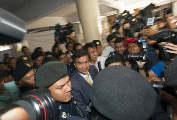 Former Thai prime minister Abhisit Vejjajiva (C) arrives at the Bangkok Metropolitan Police headquarters on Dec. 9, 2011 for questioning over a deadly military crackdown he oversaw on mass opposition protests in Bangkok in April and May of 2010. (Joan Manuel Baliellas/AFP/Getty Images)