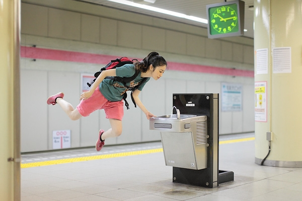 "Natsumi Hayashi levitates in front of a public drinking fountain in her image ""May 6, 2011."" (Natsumi Hayashi)"