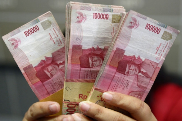An Indonesian clerk holds stacks of Indonesian rupiah notes at a currency exchange office in Jakarta on Sept. 4, 2013. (Adek Berry/AFP/Getty Images)