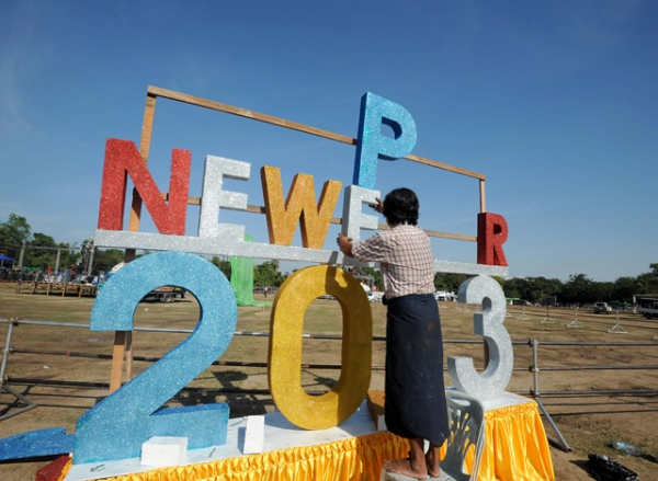 A worker puts up a sign to bring in the new year ahead of Myanmar's first public New Year countdown celebration at the Myoma grounds in Yangon, Myanmar on December 31, 2012. (Soe Than WIN/AFP/Getty Images)