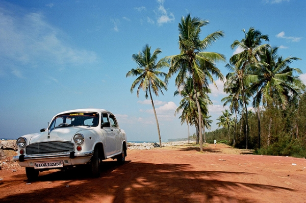 A white car sits stationary by the water in Kerala, India on January 24, 2013. (julien mrt/Flickr)