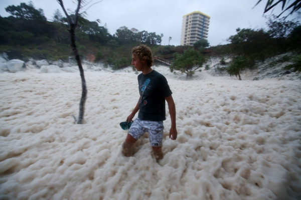 A man walks through ocean foam in Snapper Rocks as Queensland experiences severe rains and flooding from Tropical Cyclone Oswald in Gold Coast, Australia on January 28, 2013. (Chris Hyde/Getty Images)