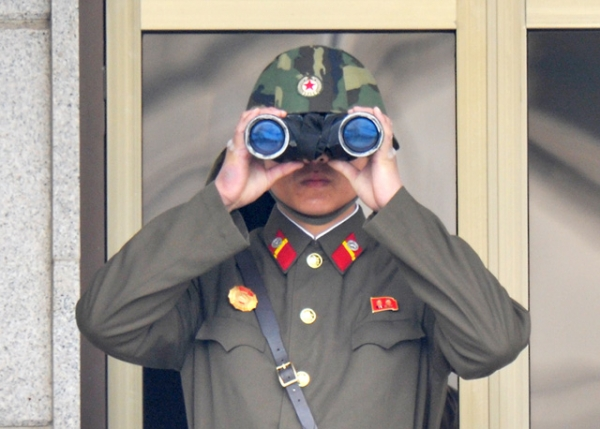 A North Korean soldier using binoculars watches from his quarters at the truce village of Panmunjom in the demilitarized zone on April 23, 2013. (Kim Jae-Hwan/AFP/Getty Images)