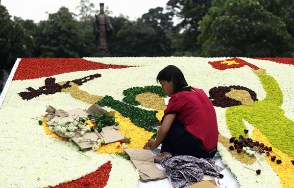 A worker uses plastic flowers to build a display marking the 38th anniversary of the end of the Vietnam War at a public park in the centre of Hanoi on April 24, 2013. (Hoang Dinh Nam/AFP/Getty Images)