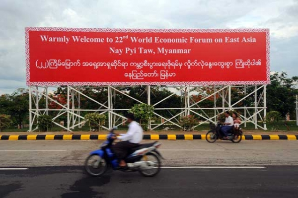 Locals ride motorcycles past a billboard for the 22nd World Economic Forum on East Asia, held this year in Myanmar's capital city of Naypyidaw, on June 3, 2013. (Soe Than WIN/AFP/Getty Images)
