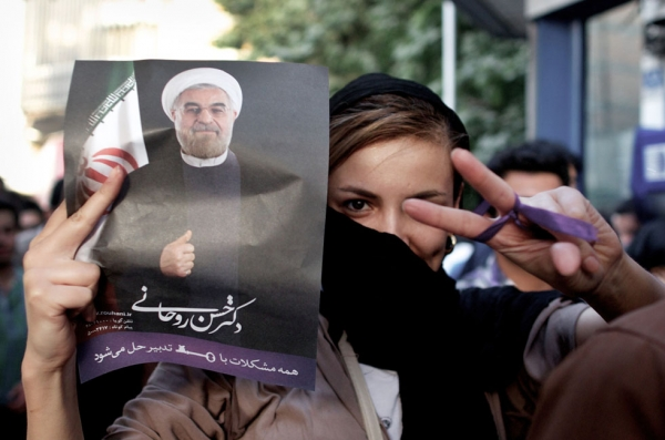 An Iranian woman flashes a victory sign as she holds a portrait of moderate presidential candidate Hassan Rouhani during celebrations in downtown Tehran, June 15, 2013. Iran's Interior Minister has said Rouhani won the election with 18.6 million votes, or 50.68 percent of the vote. (Behrouz Mehr/AFP/Getty Images)