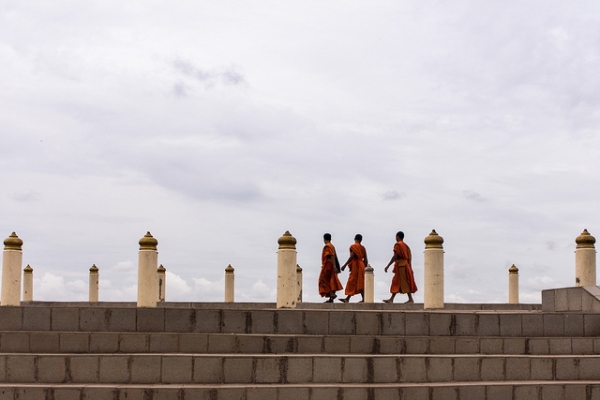 Three monks hurry across the stone steps under a cloudy sky in Vientiane, Laos on June 20, 2013. (Samuel Chan/Flickr)