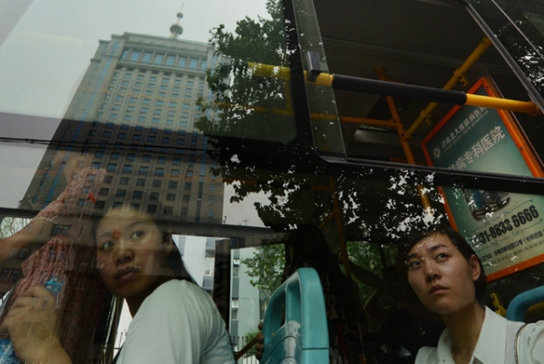 Commuters look at the Intermediate People's Court — where Bo Xilai was indicted and his case is expected to be heard — reflected in a bus window in Jinan, Shandong province on July 25, 2013. (Mark Ralston/AFP/Getty Images)