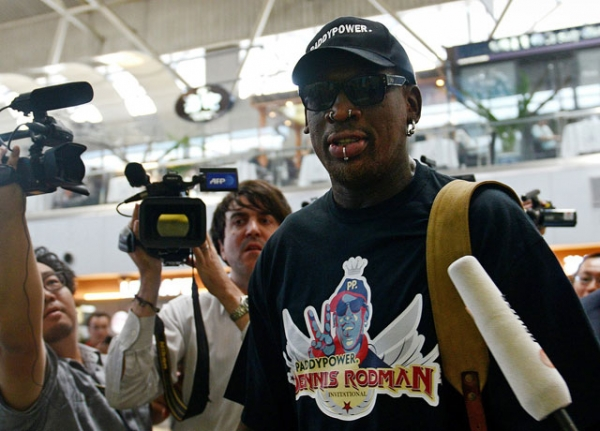 "Former NBA basketball player Dennis Rodman is surrounded by members of the media as he makes his way through Beijing's international airport on September 3, 2013. Rodman said he was heading back to Pyongyang to see his ""friend,"" North Korean leader Kim Jong Un, but refused to say if he would come back with an imprisoned US citizen. (Wang Zhao/AFP/Getty Images)"