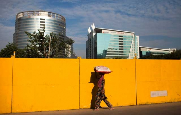 A pedestrian walks past a construction site near corporate offices in Gurgaon, on the outskirts of New Delhi, India on October 5, 2013. (Andrew Caballero-Reynolds/AFP/Getty Images)