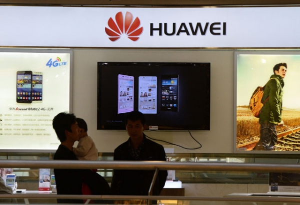 Shoppers walk past a Huawei store in Beijing on March 24, 2014. Chinese telecoms and Internet giant Huawei condemned the U.S. National Security Agency on March 24 after reports revealed the organization had been secretly tapping the company's networks for years. (Mark Ralston/AFP/Getty Images)