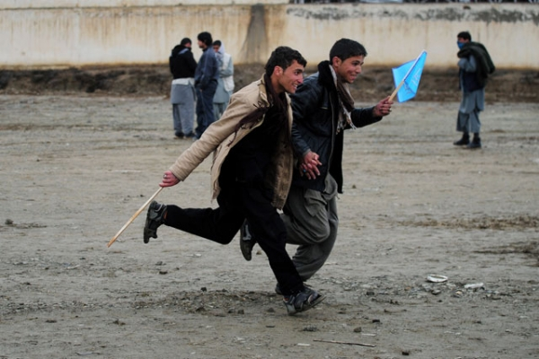 Supporters run to get a spot near the stage at an election rally for presidential candidate Abudullah Abdullah on the outskirts of Kabul on April 2, 2014, the last day of campaigning by Afghanistan's presidential candidates. (Roberto Schmidt/AFP/Getty Images)