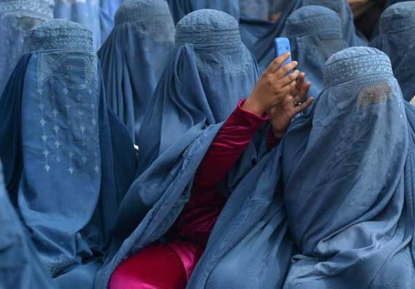 An Afghan woman takes a photograph with her mobile phone at an election rally in Jalalabad on February 18, 2014. Smartphone technology, writes Ahmad Shuja, played a vital role in ensuring a free and fair election for Afghanistan in April 2014. (Shah Marai/AFP/Getty Images)