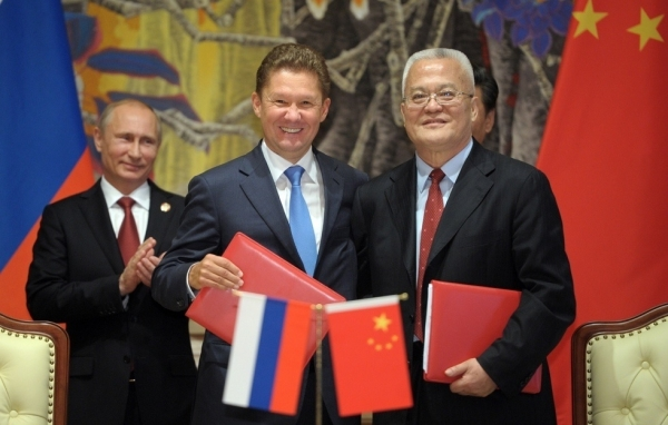 Russia's President Vladimir Putin (L) applauds during the agreement signing ceremony in Shanghai on May 21, 2014, with Gazprom CEO Alexei Miller (C) and Chinese state energy giant CNPC Chairman Zhou Jiping (R) attending the ceremony. (Alexey Druzhinin/AFP/Getty Images)