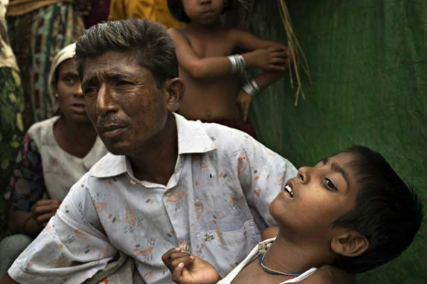 Roshida Moud, 12, is held by his father as the latter explains that his son was hit in the head with a stone during the Rakhine violence in 2012, in Sittwe, Myanmar, on May 6, 2014. (Andre Malerba/Getty Images)