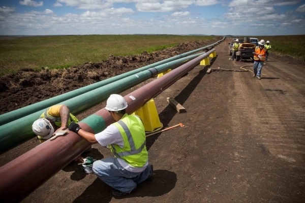 Construction workers specializing in pipe-laying work on a section of pipeline on July 25, 2013 outside Watford City, North Dakota. (Andrew Burton/Getty Images)