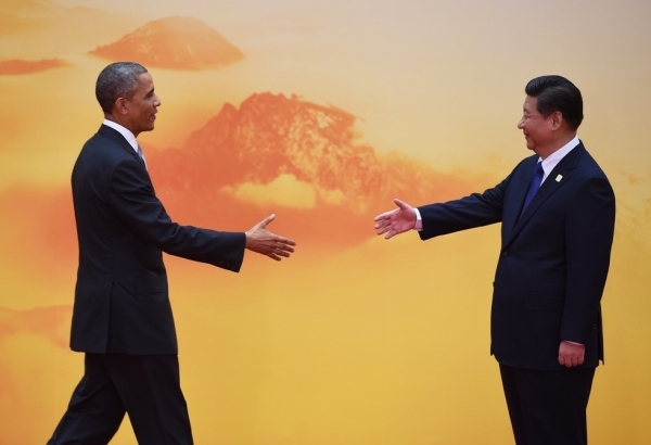 U.S. President Barack Obama is greeted by Chinese President Xi Jinping as he arrives for the Asia-Pacific Economic Cooperation (APEC) leaders meeting at Yanqi Lake, north of Beijing on November 11, 2014. (Greg Baker/AFP/Getty Images)
