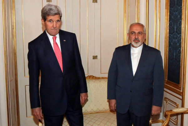 Close, but not quite there: U.S. Secretary of State John Kerry (L) and Iranian Foreign Minister Mohammad Javad Zarif prior to closed-door nuclear talks at the Palais Coburg in Vienna on Nov. 23, 2014. Asia Society's Tom Nagorski predicts a nuclear deal will be signed in 2015. (Ronald Zak/AFP/Getty Images)