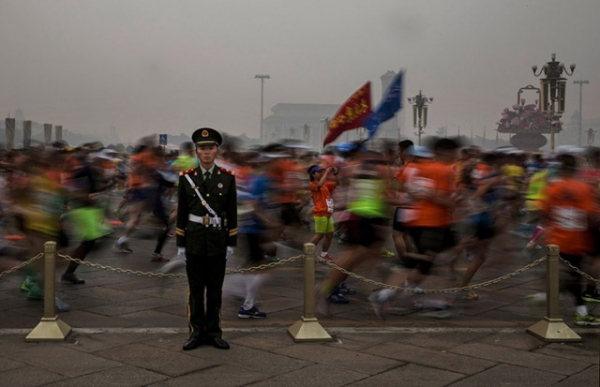 Runners in masks file past a soldier during the Beijing Marathon. (Kevin Frayer/Getty Images)