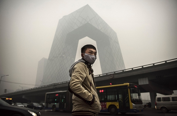 A man wears a mask as he waits to cross the road near the CCTV building in Beijing during heavy smog on November 29, 2014. (Kevin Frayer/Getty Images)
